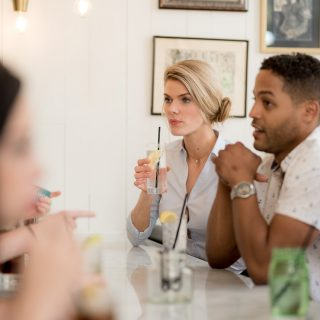 A man and a woman having drinks at a restaurant table