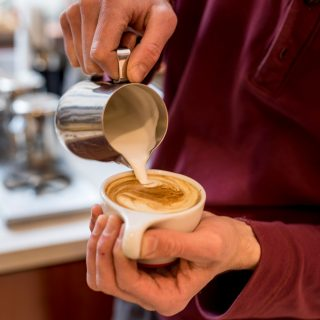 Man creating beautiful latte art in cafe near Old City on Market