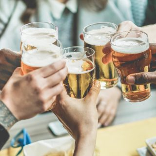 Five beer glasses being clinked together for a toast