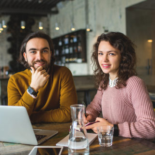 Man and woman working together on a laptop at a co-working space