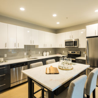 furnished kitchen with white cabinets and stainless steel appliances in old city apartment for rent