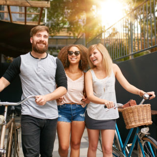 Three people laughing while walking with bikes
