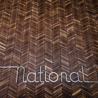 Interior sign at The National, with wooden herringbone design